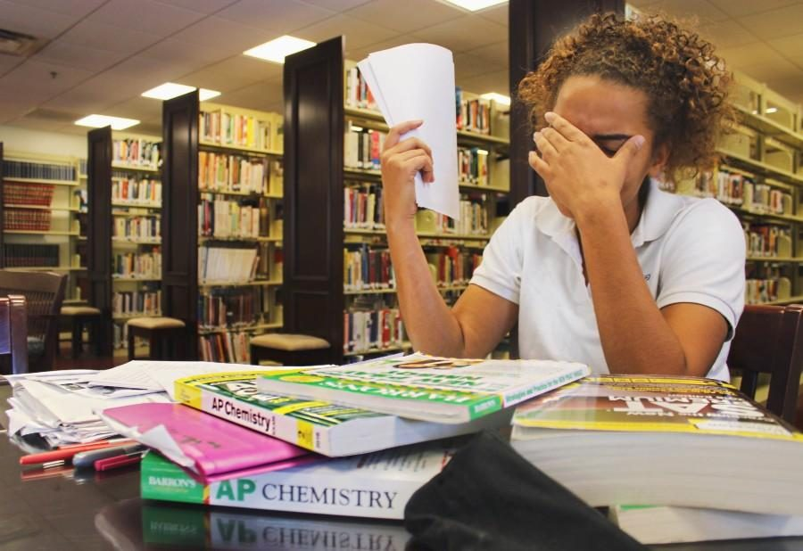 Student drowning in the ap books and study guides for the approaching exams.