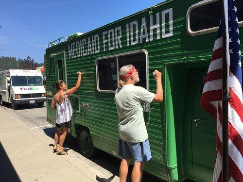 "Supporters of ""Reclaim Idaho"", the campaign supporting the expansion of Medicaid, sign their names on the infamous green Medicaid bus."