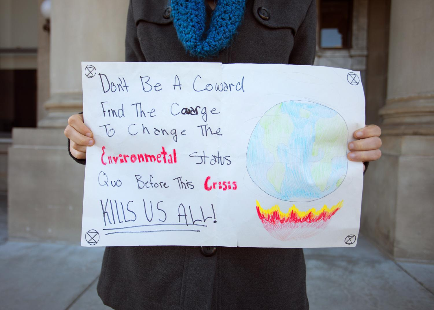 Camden Mullens, with her climate strike protesting poster.