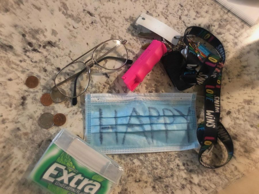 "A scattering of everyday items along with a mask to show how masks have become incorporated into daily life. Additionally, the mask has the word ""happy"" written on it to show how as a society we often hide our negative emotions and only display positive things to make us look our best on social media."