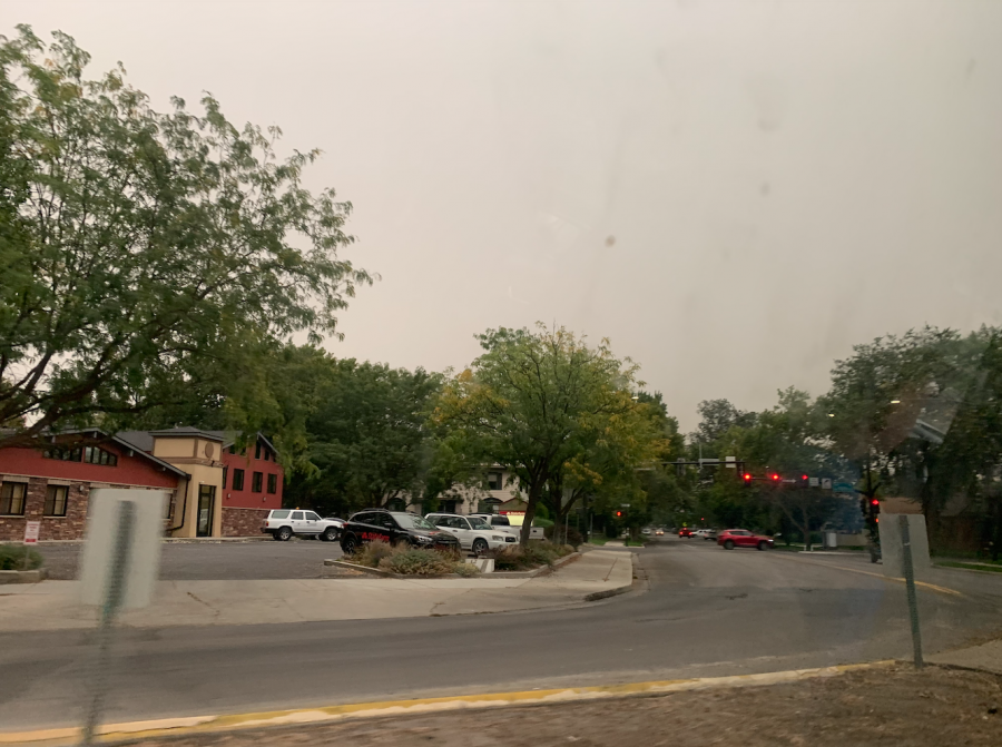 A grey sky, filled with smoke appearing on a rainy day.