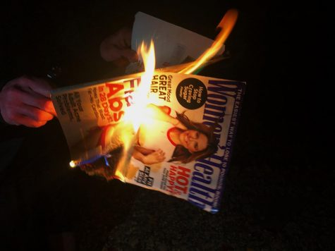A magazine with a dieting advertisement on the cover being burned to represent destroying the dangerous ideals that dieting culture creates. (Bella Rock)