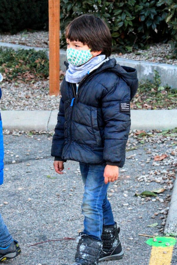 A kindergarten student playing outside with his friends. Face coverings and social distancing is required.